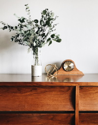 brown analog mantle clock next to greenery on a console
