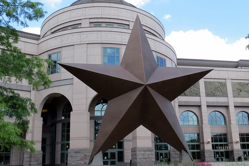 a large three-dimensional five pointed star in front of a museum building.